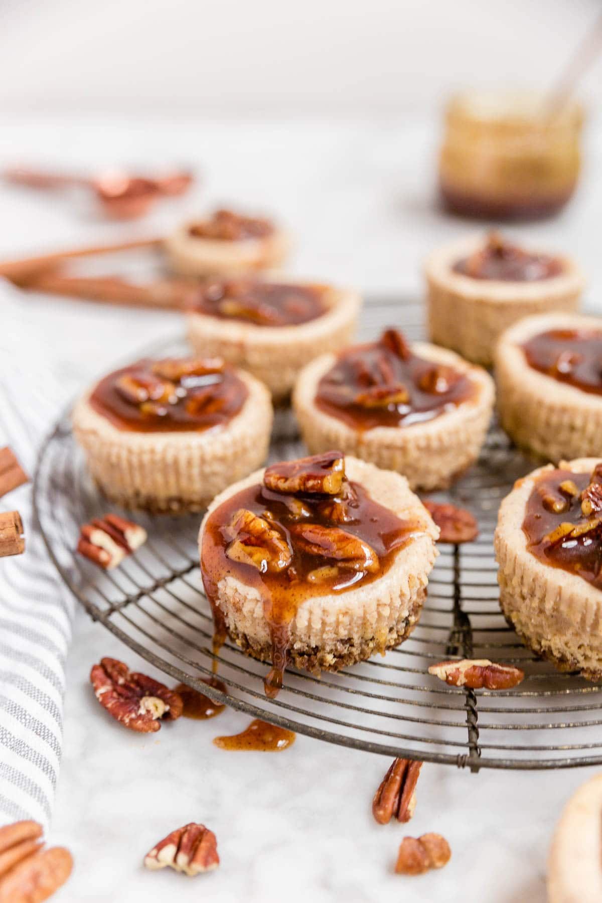 A cooling rack with mini pecan pie cheesecakes dripping with pecan pie caramel sauce ready for serving.
