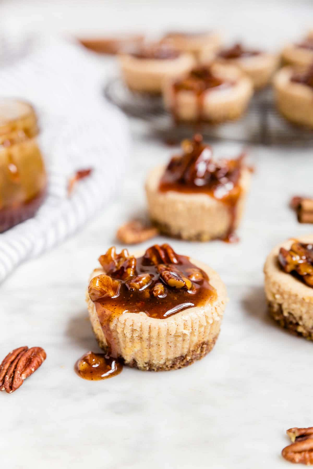 A mini pecan pie cheesecake with decadent caramel sauce with toasted pecans on top.