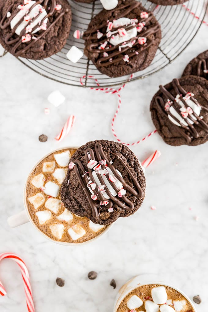 A chocolate peppermint hot chocolate cookie on top of a mug of hot chocolate with mini marshmallows and a baking rack with gluten-free peppermint hot chocolate cookies on it.