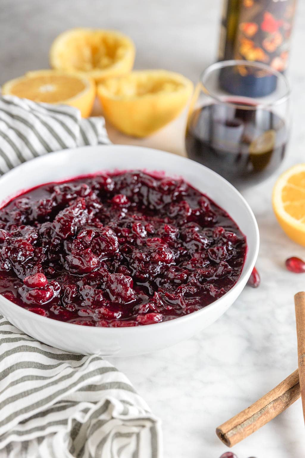 A white bowl filled with red wine cranberry sauce with orange juice, cinnamon and sugar for an easy holiday recipe.