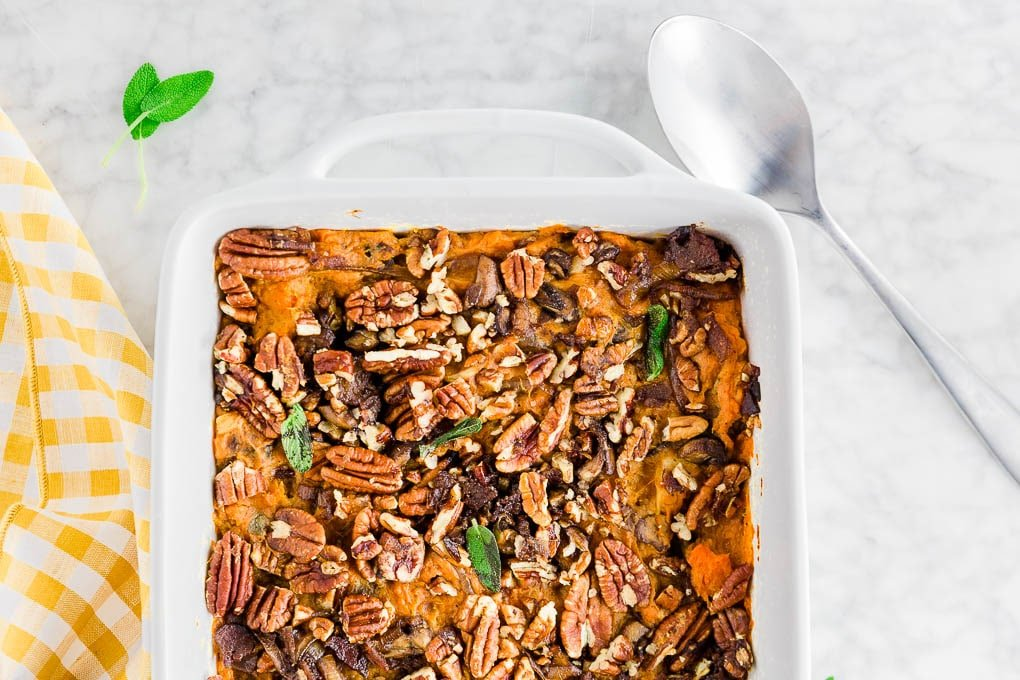 A baking dish with easy savory sweet potato casserole that is both gluten-free and dairy-free, topped with bacon, caramelized onions, mushrooms, sage and pecans.