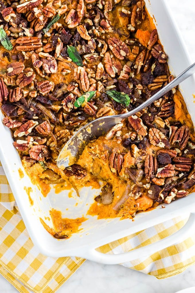 A baking dish with gluten-free savory sweet potato casserole topped with pecans, caramelized onions, bacon, mushrooms and sage with a spoon digging in.