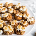 A plate with sweet potato casserole bites with a gluten-free brown sugar pecan crumble and toasted marshmallows with a bowl of pecans.