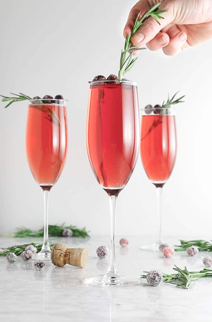 A cranberry mimosa with a sprig of fresh rosemary being placed on top for garnish.