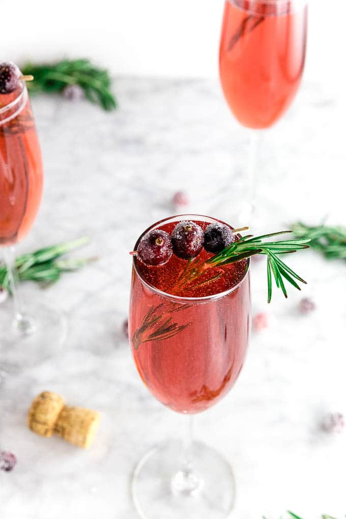 three champagne flutes filled with cranberry juice and prosecco with sugared cranberries and fresh rosemary in a festive cranberry mimosa cocktail