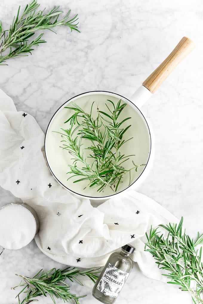 a pot of rosemary simple syrup steeping with a bottle of rosemary infused simple syrup, fresh rosemary sprigs and a cup of sugar.
