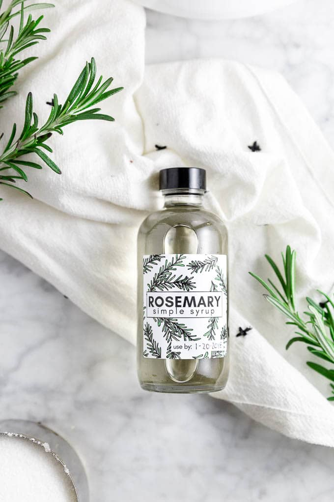 a bottle of rosemary simple syrup with fresh rosemary sprigs and sugar