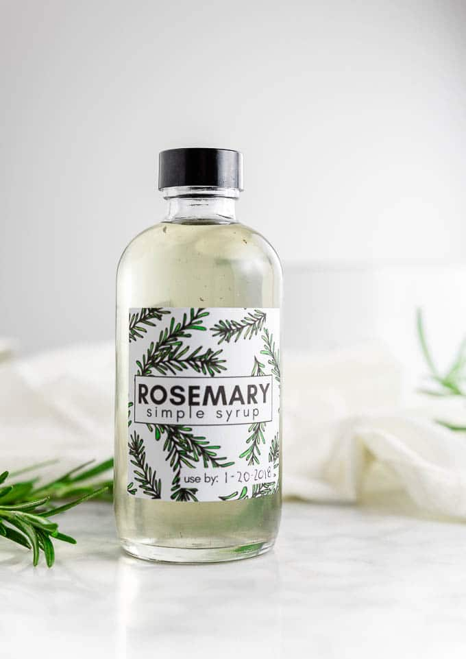 A bottle of rosemary simple syrup with fresh rosemary and sugar.