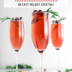 three champagne flutes filled with cranberry mimosa topped with rosemary and sugared cranberries