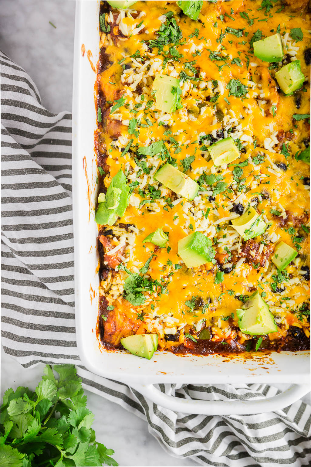 A white baking dish filled with chicken enchilada casserole topped with shredded cheese, avocado slices, and chopped cilantro.