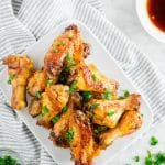 A plate of baked honey garlic chicken wings topped with green onions on a white table with a side of honey garlic sauce.
