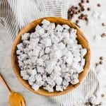 Dairy-free puppy chow in a wooden bowl with a spoonful of peanut butter and chocolate chips and powdered sugar on a linen napkin and table.