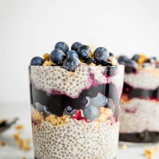 A glass filled with layered chia seed pudding with granola, jam and fresh blueberries.