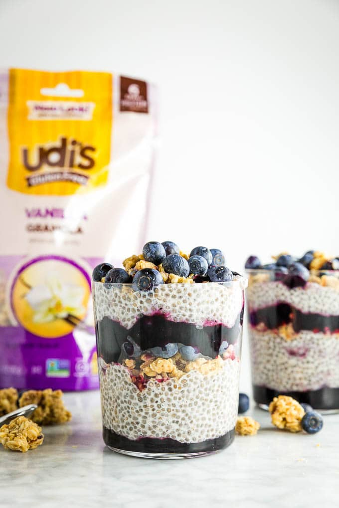 A glass of chia seed pudding layered with Udi's granola, blueberry jam and fresh blueberries with a bag of Udi's Gluten Free Vanilla Granola in the background.