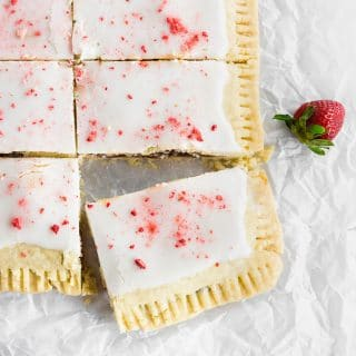 A photo of a giant strawberry pop tart covered with a powdered sugar glaze and freeze dried strawberries.