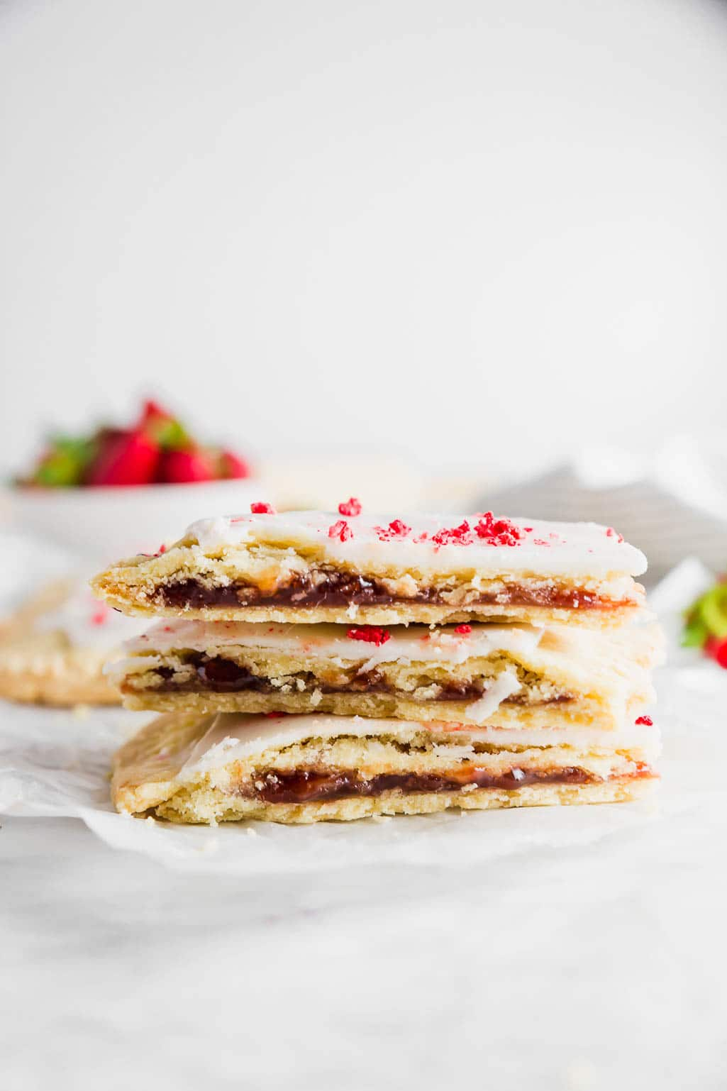 A stack of three gluten-free strawberry pop tarts with a bowl of fresh strawberries.