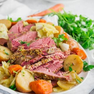 A photo of a platter of corned beef with potatoes, carrots, parsley, cabbage and onions.