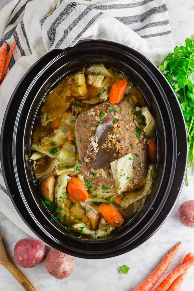 A photo of a crock pot with corned beef, carrots, onion, cabbage and potatoes.