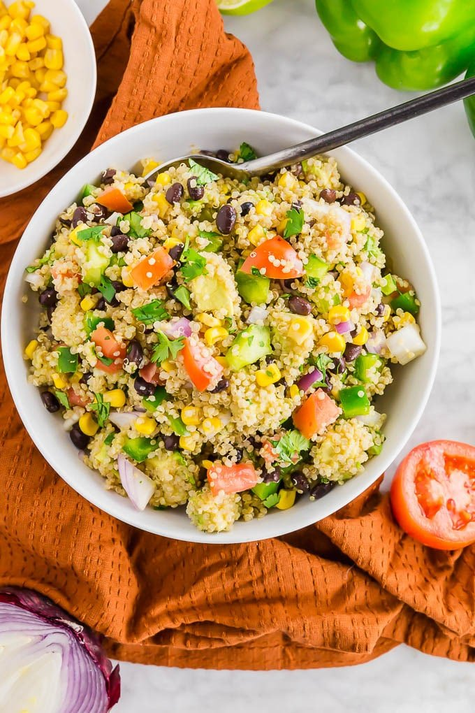 a bowl of southwest quinoa salad with tomatoes, avocado, red onion, cilantro, corn and black beans.