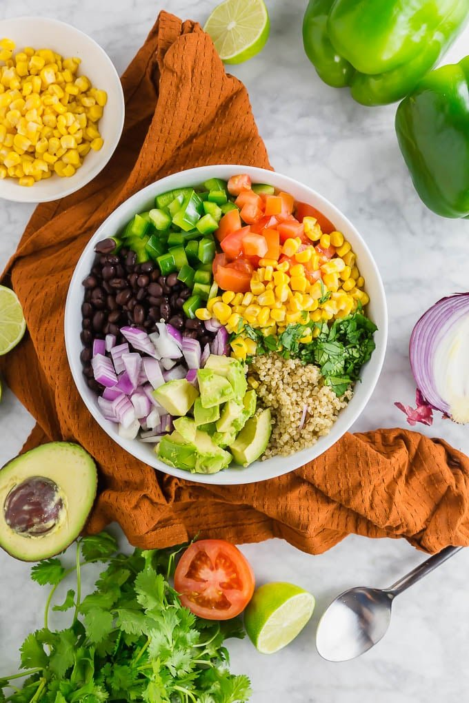 A bowl filled with quinoa, black beans, bell pepper, tomato, corn, cilantro, avocado and red onion.