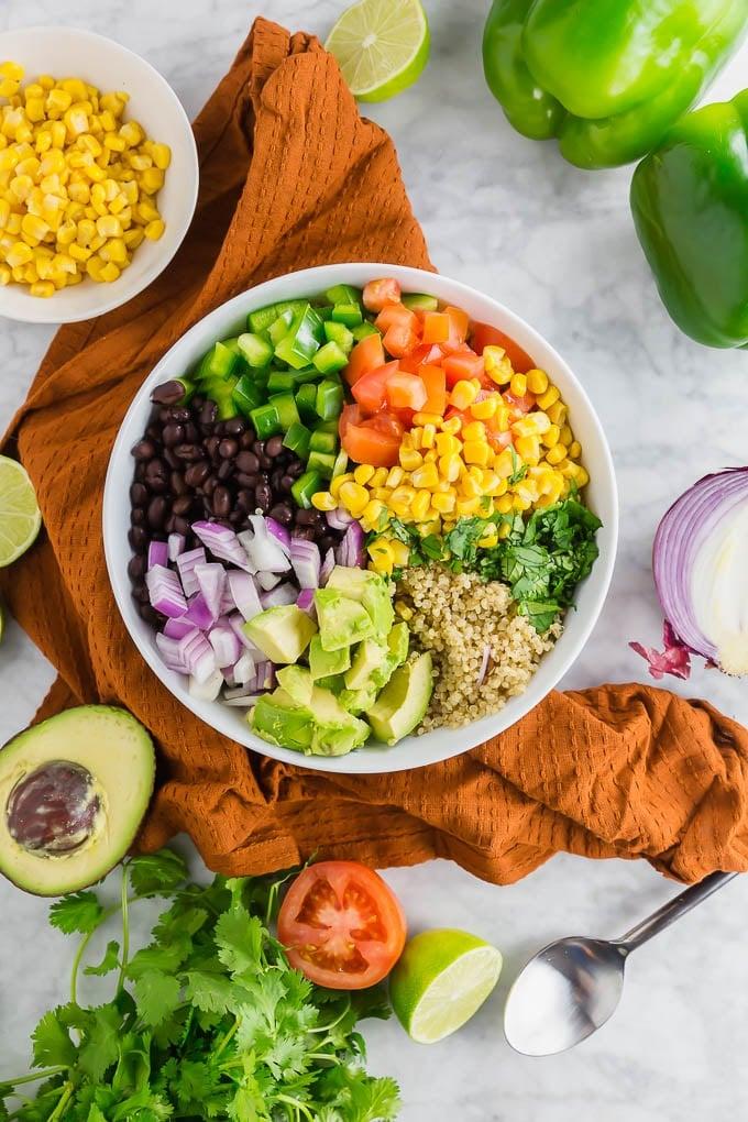 A bowl filled with quinoa, black beans, bell pepper, tomato, corn, cilantro, avocado and red onion.