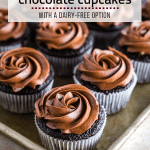 Photo of a sheet pan filled with a dozen gluten-free chocolate cupcakes with chocolate buttercream frosting.