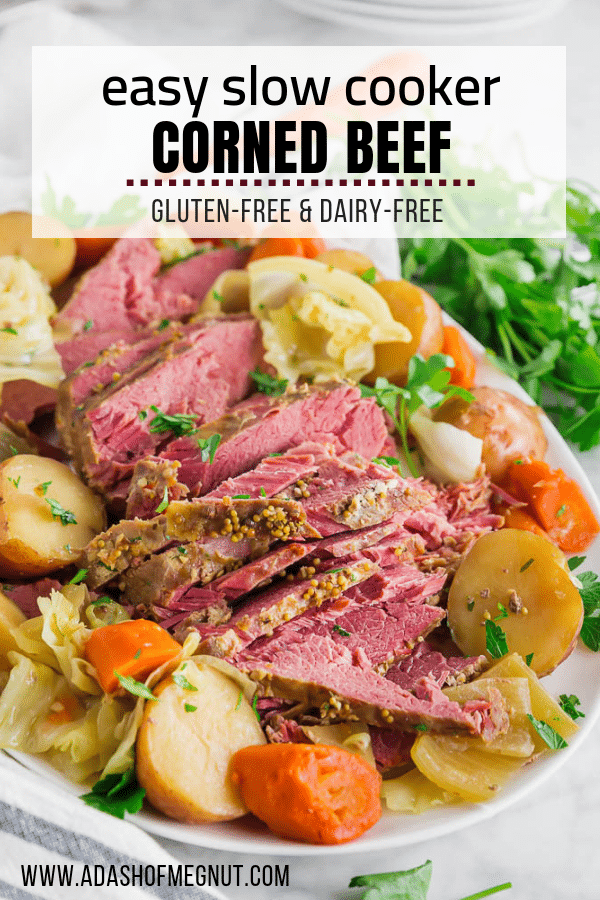 A platter of crock pot corned beef with red potatoes, carrots, cabbage, onion and fresh parsley.
