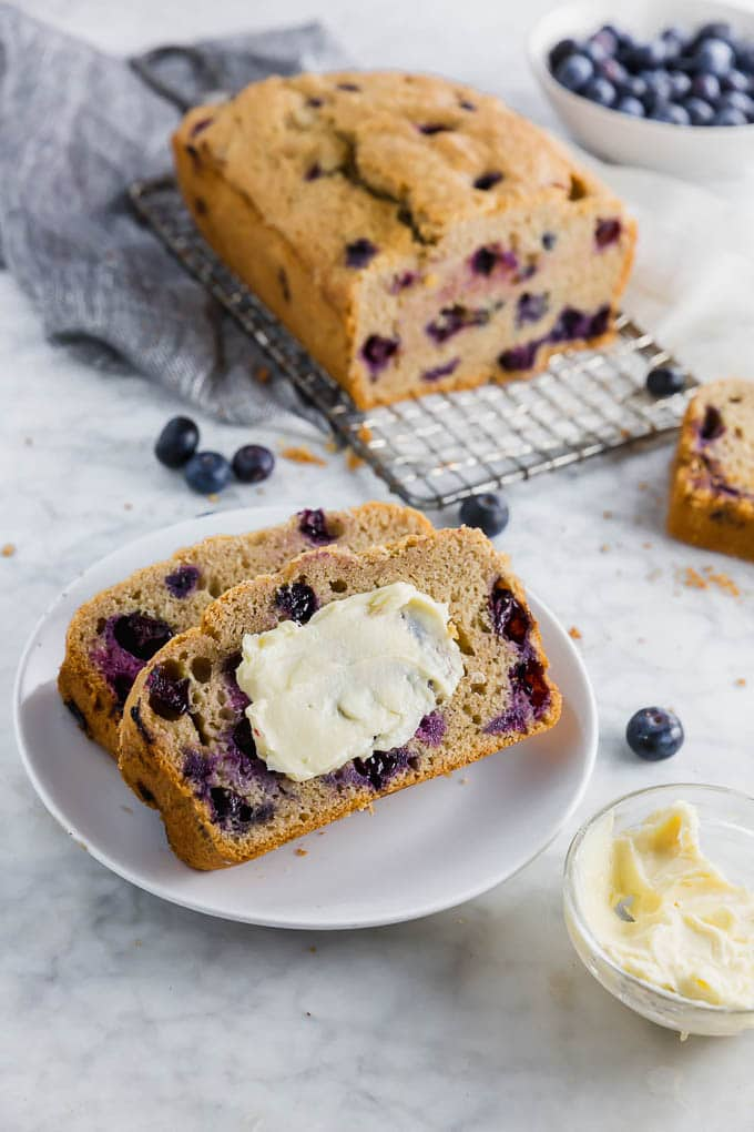 A loaf of blueberry muffin bread with two slices on a small plate slated in dairy free butter.