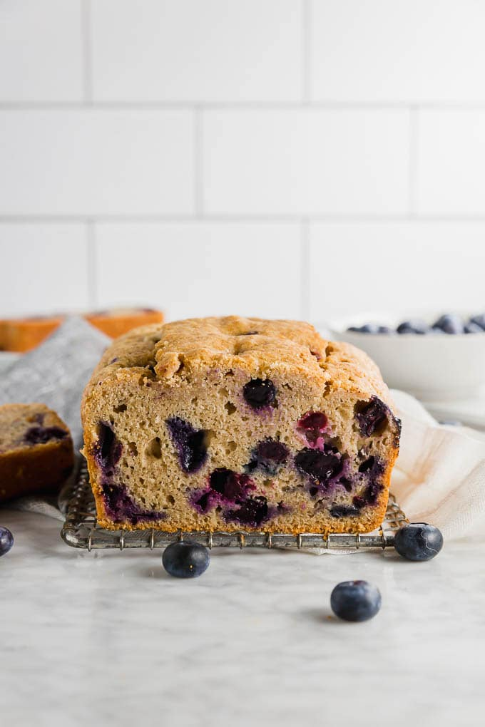 A loaf of gluten free blueberry muffin bread on a table with fresh blueberries.