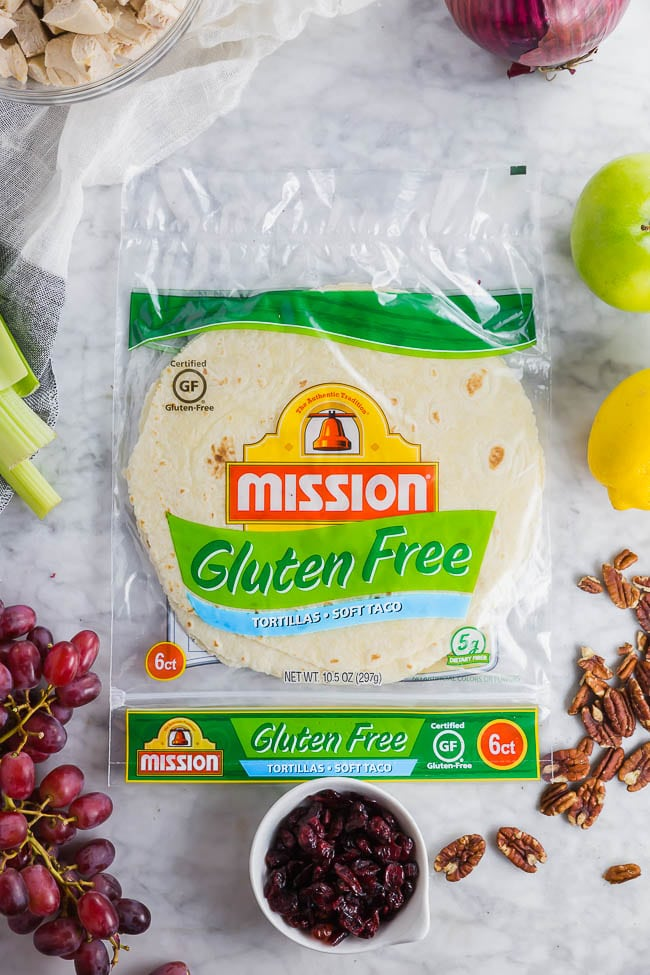 A photo of a package of Mission Gluten Free Tortillas surrounded by grapes, dried cranberries, celery, pecans, apples, red onion and chicken to make a gluten free chicken salad.