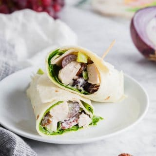 A photo of two gluten free chicken salad wraps on a plate with red onions and red grapes in the background.