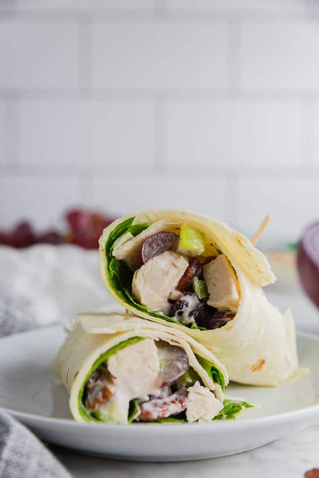 Photo of two gluten free chicken salad wraps on Mission Gluten Free tortillas on a plate with grapes.