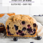 A loaf of gluten free blueberry muffin quick bread on a table with fresh blueberries.
