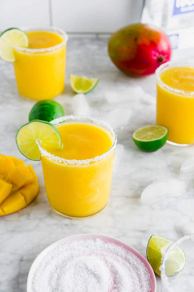 A photo of frozen mango margaritas, a plate with kosher salt, limes, fresh mangos and a bottle of tequila.