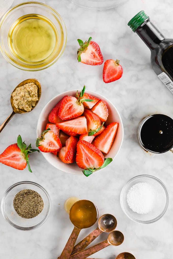A photo of sliced strawberries, ground mustard, olive oil, balsamic vinegar, salt, pepper and honey on a marble table.