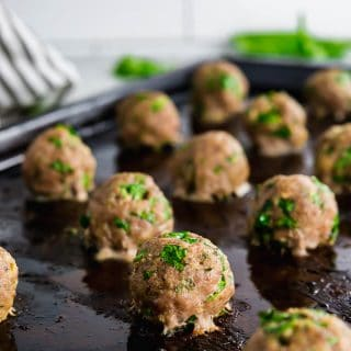 A sheet pan with baked turkey spinach meatballs straight from the oven with fresh spinach in the background.