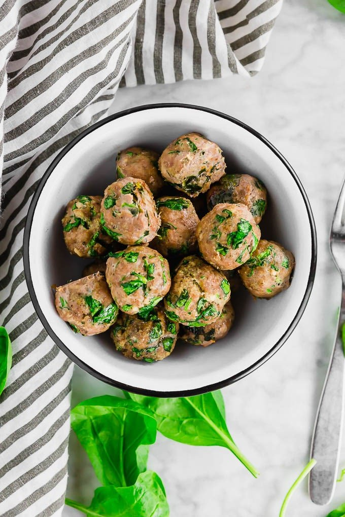 An overhead photo of a bowl of gluten free baked turkey meatballs filled with fresh spinach.