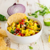A bowl of homemade mango salsa with bell peppers, cilantro, and jalapeño in a bowl with a tortilla chip.