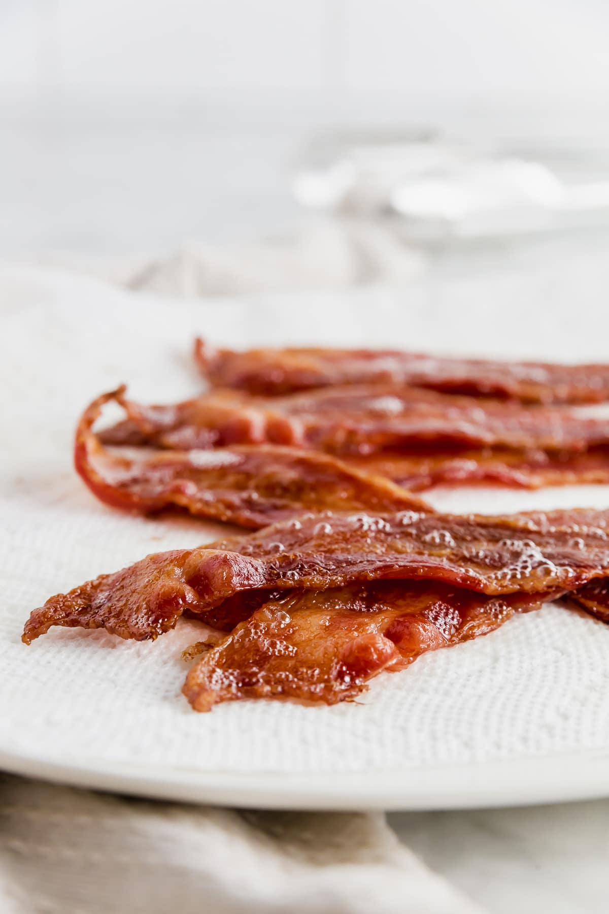 A plate covered with a paper towel and bacon straight fro the oven.