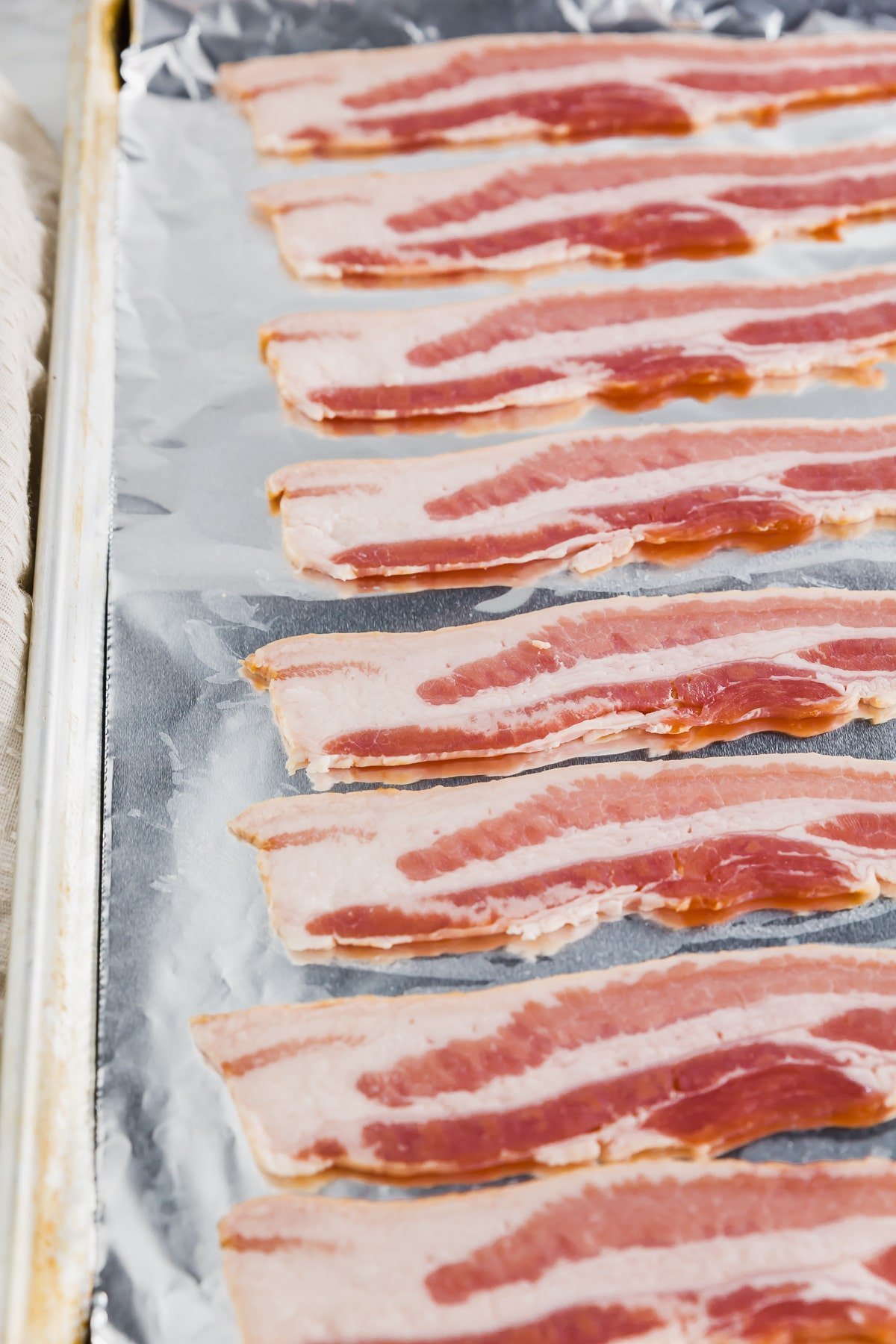 A baking sheet covered with aluminum foil and topped with bacon ready to be baked in the oven.