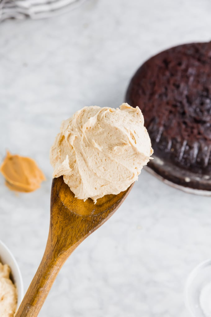 A photo of a wood spoon with peanut butter frosting on it with a gluten-free chocolate cake in the background.