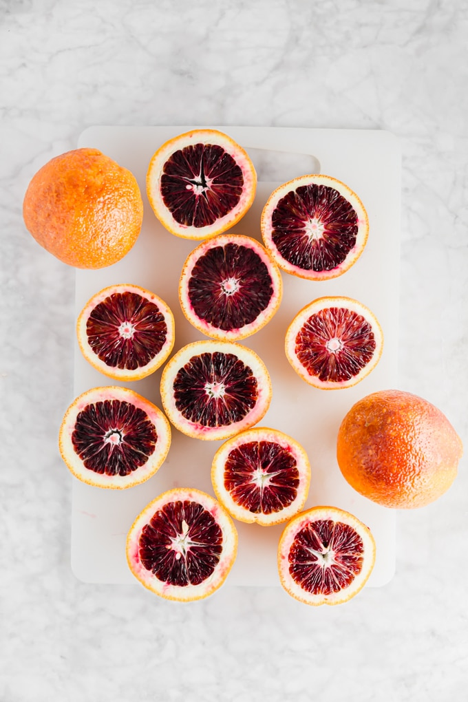 An aerial view of blood orange sliced open on a cutting board.