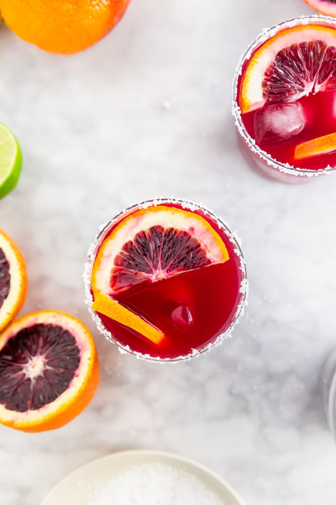 A aerial view of a blood orange margarita on the rocks with sliced blood oranges in it.