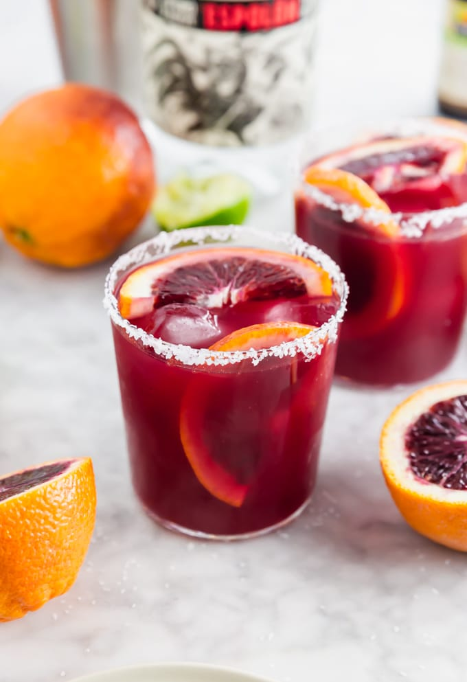 A photo of a blood orange margarita with slices of blood orange in the glass and a salted rim.