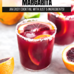 A photo of a blood orange margarita on the rocks with a salted rim and sliced blood oranges.