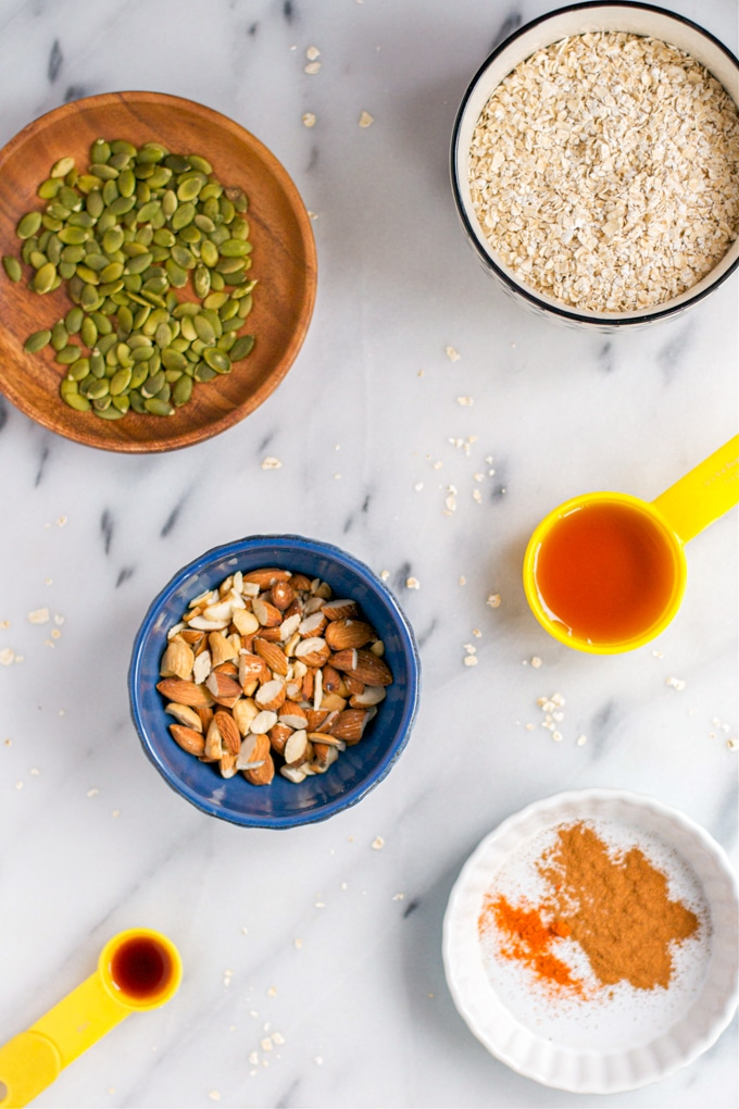 An overhead view of bowls of pumpkin seeds, oats, almonds, maple syrup, cayenne, and vanilla extract.
