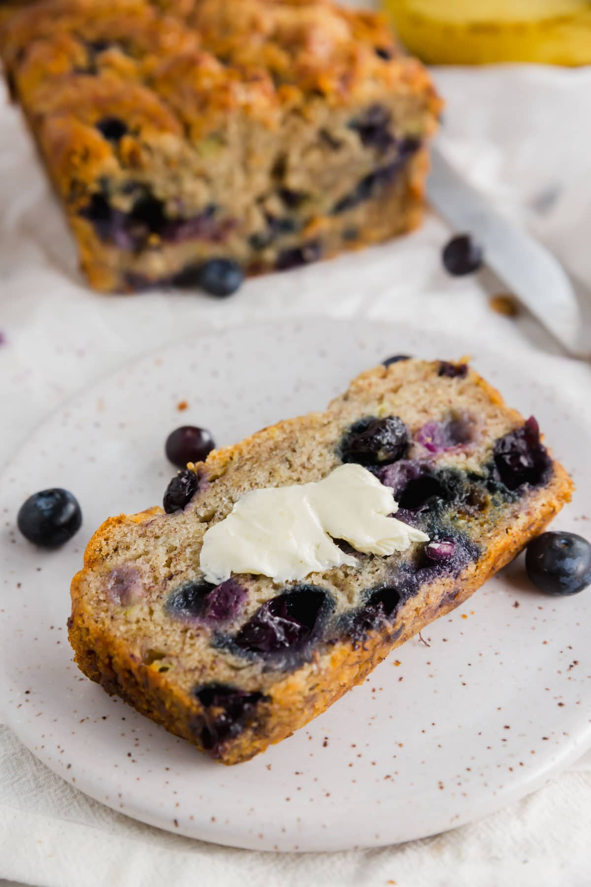A photo of a slice of gluten-free vegan blueberry banana bread with vegan butter on top with a loaf of bread in the background.