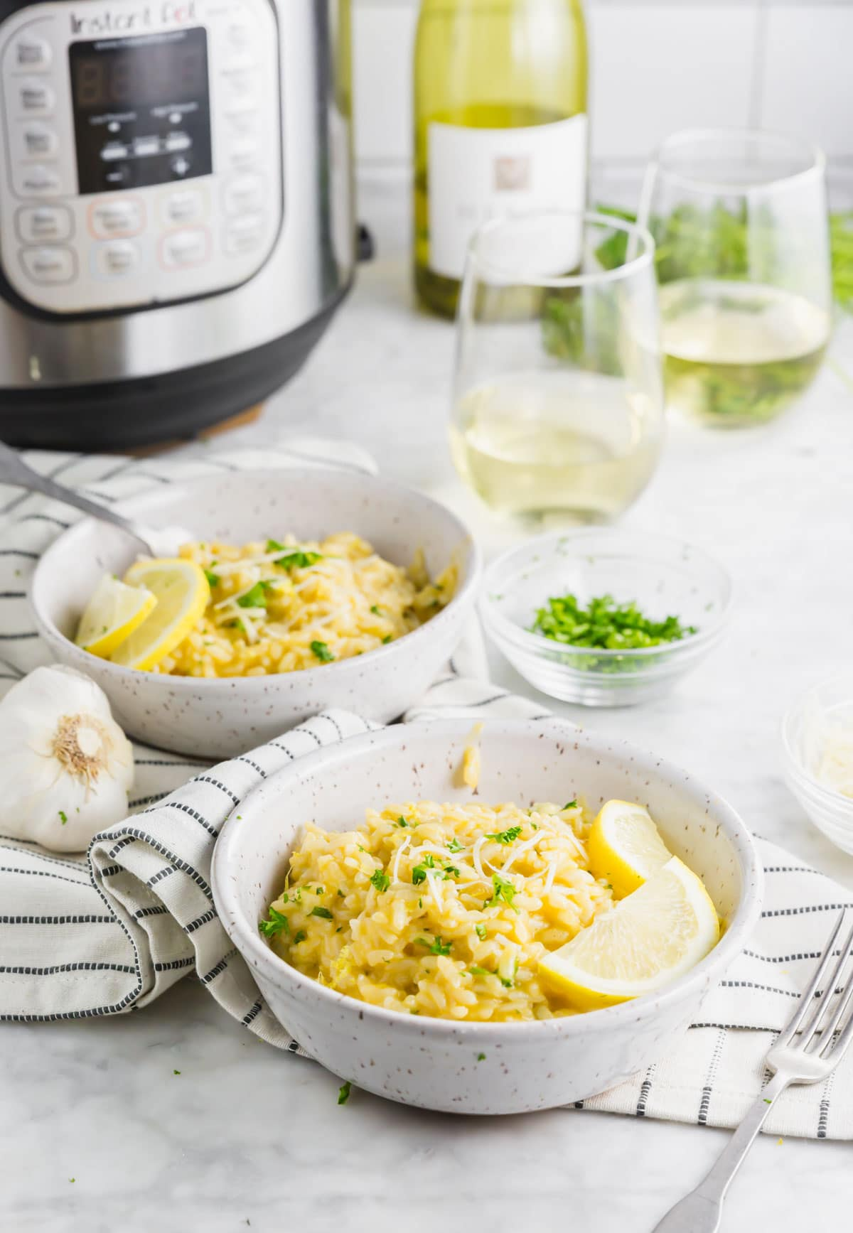 A photo of two bowls of instant pot lemon risotto with an instant pot in the background with two glasses of wine.
