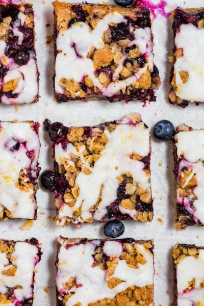 An overhead photo of nine gluten-free blueberry crumb bars with lemon glaze on a piece of parchment paper.