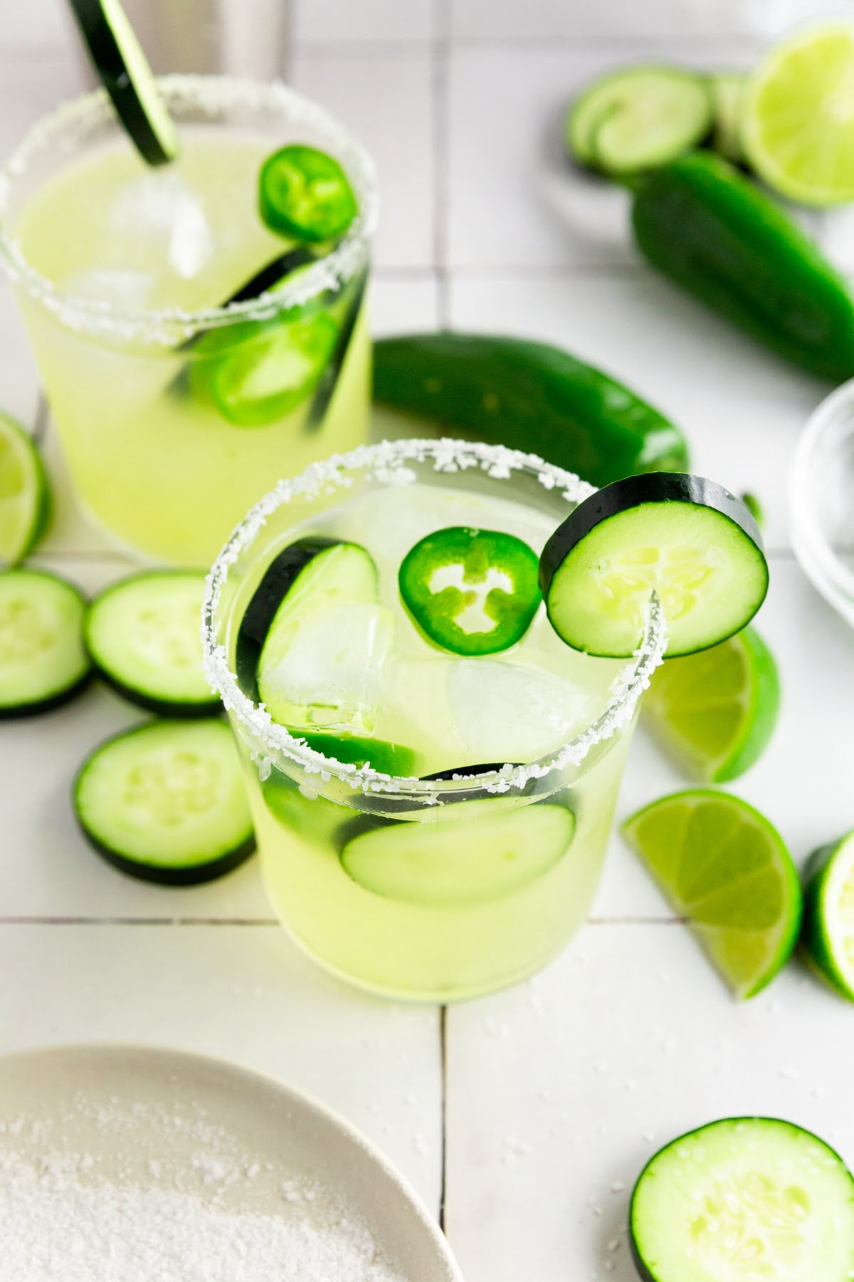 A photo of two margarita glasses filled with cucumber jalapeño margarita and rimmed with kosher salt.